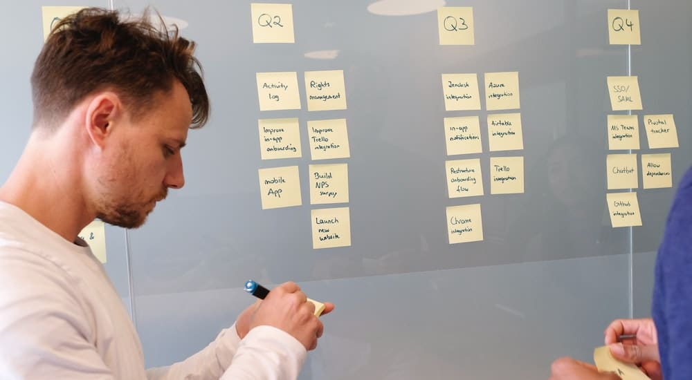 man preparing sticky notes on glass for blog post topics