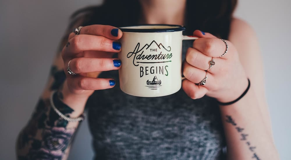 Woman holding up a coffee cup with the words the adventure begins written on it