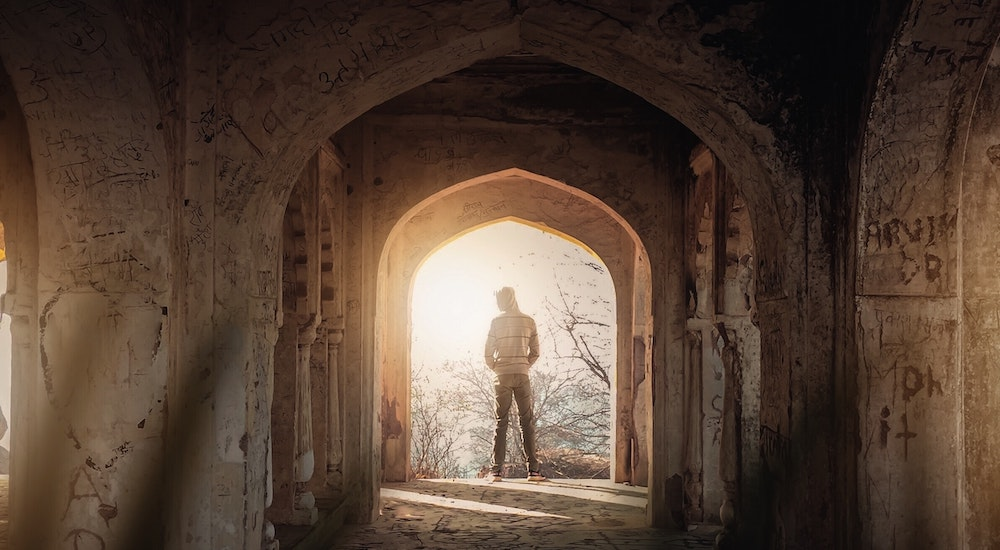 Man standing in entrance of temple with sun shining through